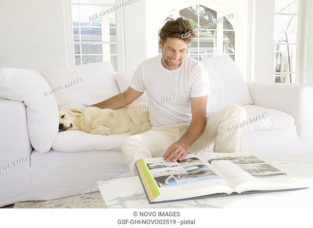 Mid-Adult Man Reading Large Book in Living Room while Petting Pet Dog II
