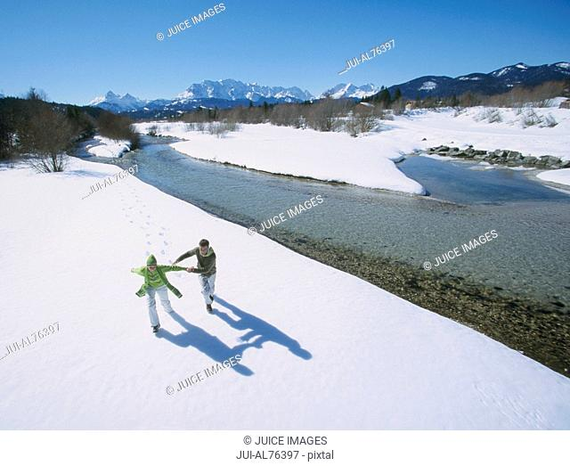 High angle view of a young couple playing in snow in winter setting, Isar, Bavaria, Germany