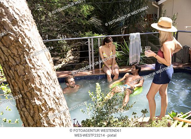 Group of friends relaxing at swimming pool