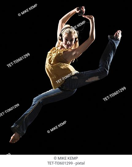 Blond woman dancing while listening to music on Mp3 player