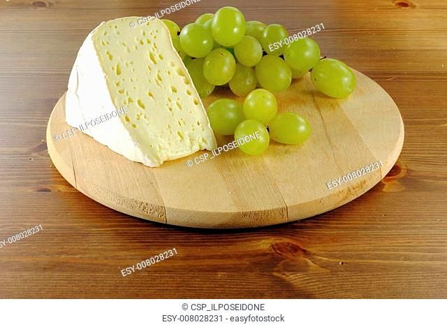 Italian cheese with grapes on wooden cutting board