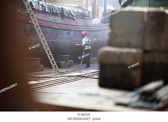 Worker sandblasting boat in shipyard