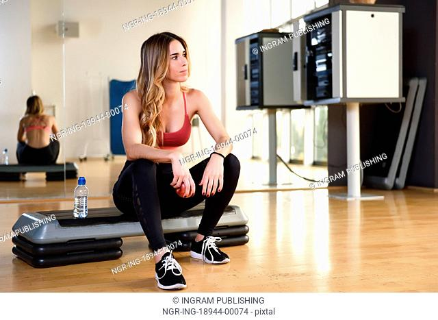 Young woman in sportswear holding an apple at gym. Girl sitting on a stepper taking a break