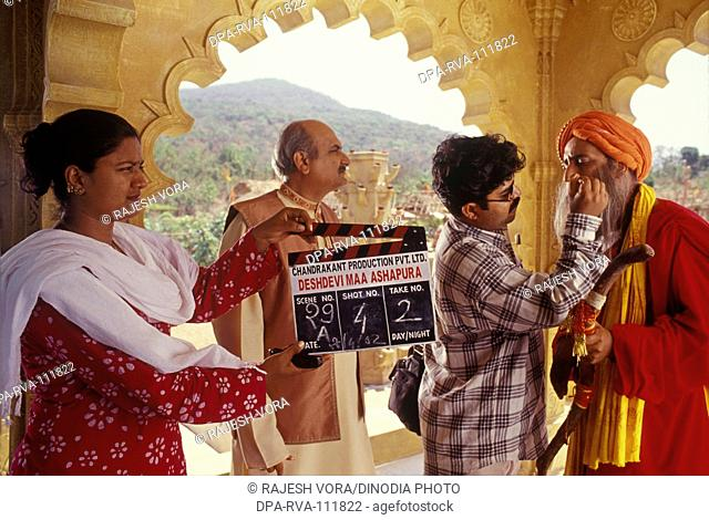A make-up artist giving final touches for a Bollywood film shoot and a clapper girl holds the clapper board before the camera , film city , Mumbai Bombay