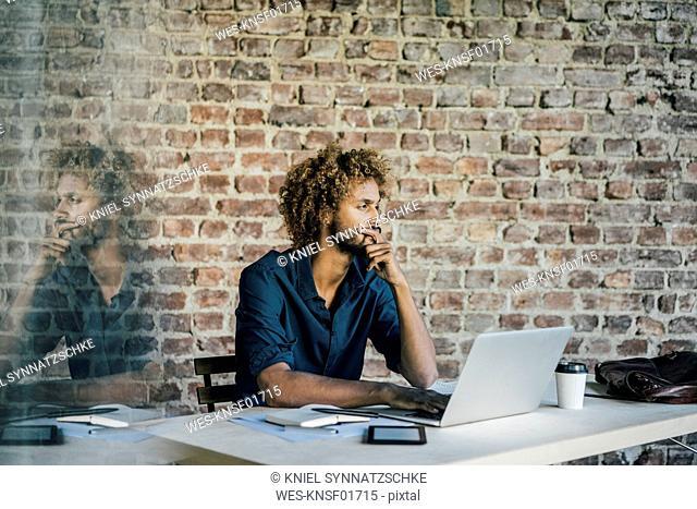 Young man at desk thinking