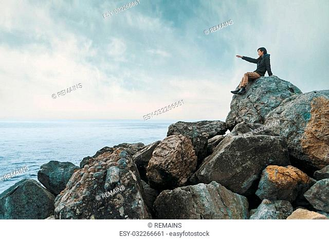 Young woman sitting on stone coast near the sea and pointing direction to somewhere. Space for text in left part of image