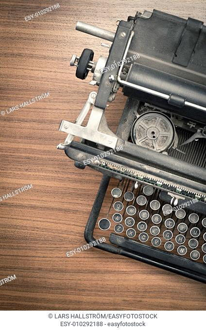 Retro vintage typewriter on wooden table. Conceptual image of old fashioned office work, communication or writing