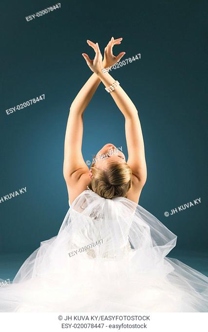 Lonely beautiful bride has arms raised, blue background, vertical format