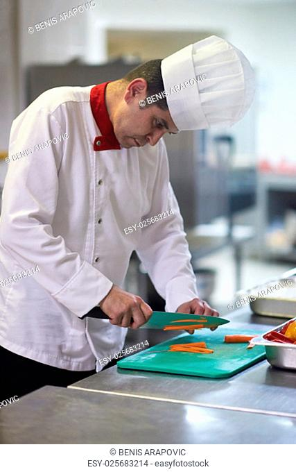 chef in hotel kitchen slice vegetables with knife and prepare food