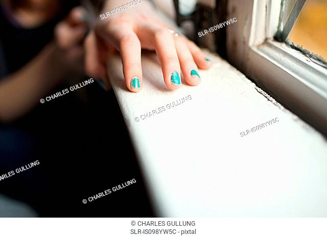 Teenage girl with hand on windowsill wearing nail varnish