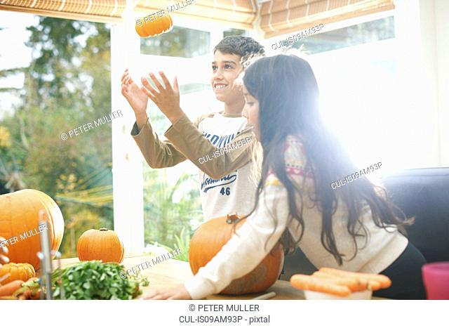 Brother and sister with homegrown pumpkins in kitchen