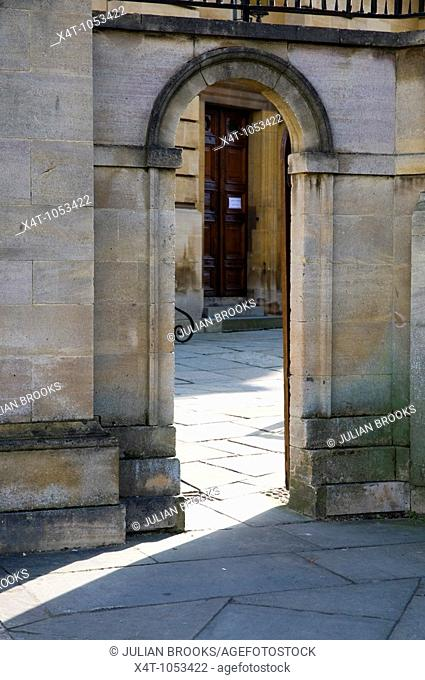 A shaft of sunlight shining through a gateway into the Sheldonian theatre Oxford