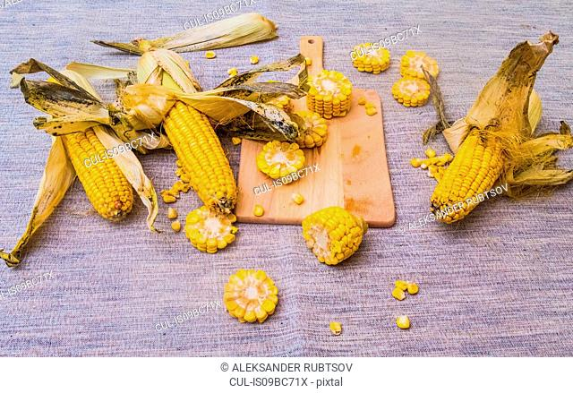 Sliced corn on the cob on chopping board, with whole corn on cob