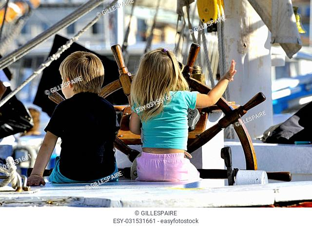 Two young children on the stand of an old wooden sailing ship cruising imagining in full
