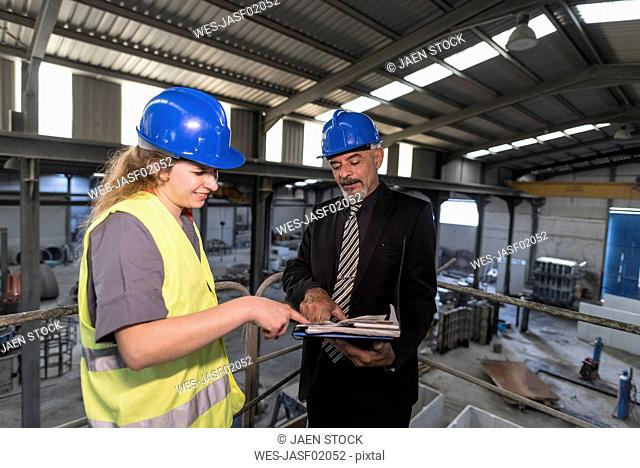 Businessman with folder talking to female worker in factory