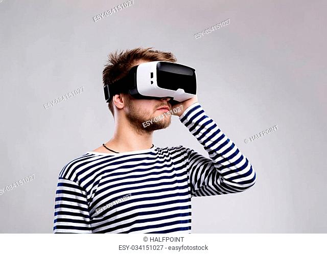 Hipster man in striped black and white sweatshirt wearing virtual reality goggles. Studio shot on gray background