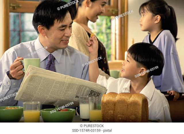 Father holding a newspaper talking to his son
