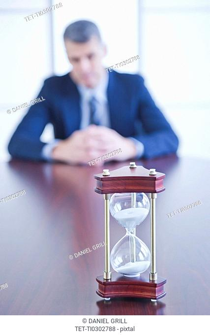 Hourglass on desk, businessman sitting on background