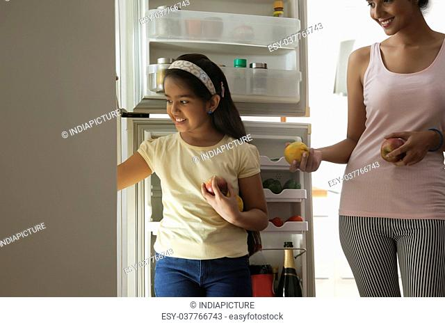 Close-up of daughter and mother putting fruits in refrigerator