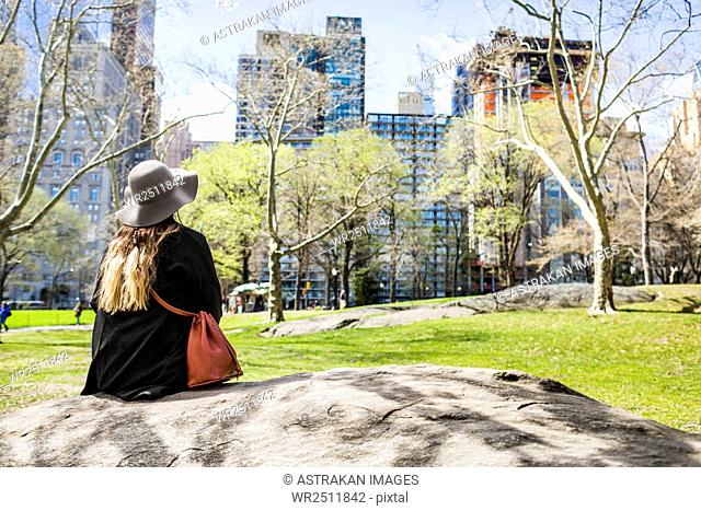 Rear view of woman sitting on rock at Central Park