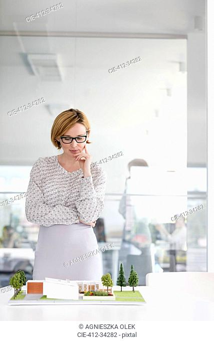 Female architect examining model in conference room