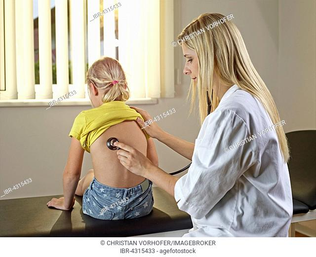 Pediatrician examining young blonde girl with stethoscope, Austria
