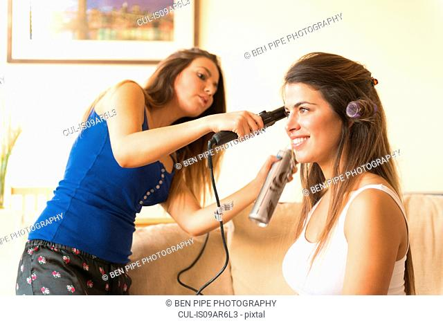 Young woman doing friend's hair