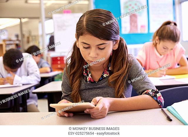 Schoolgirl using tablet computer in elementary school class