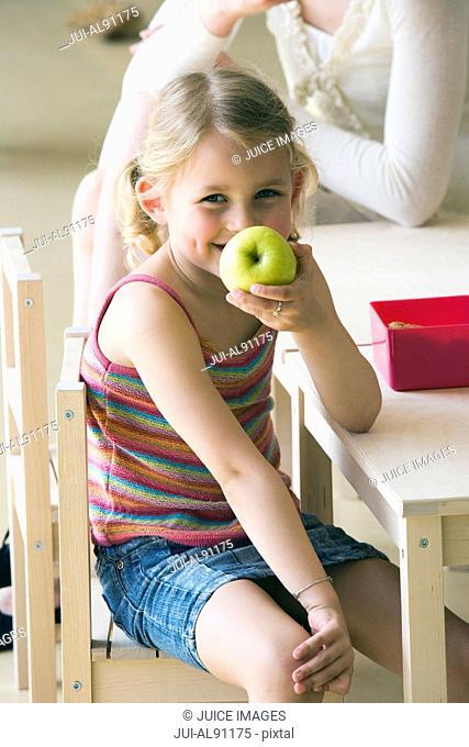 Preschool girl eating apple