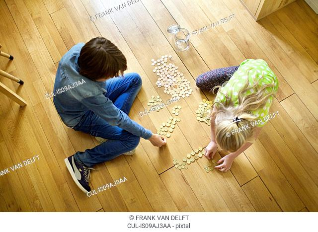 Brother and sister counting coins from savings jar