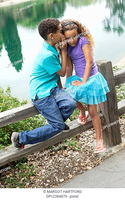 Brother and sister in a park whispering in each other's ears; Menlo Park, California, United States of America