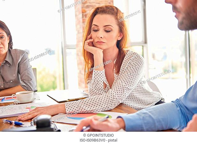 Businesswoman in meeting hand on chin looking pensive