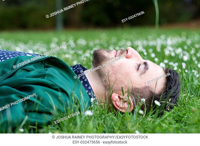 Guy in the grass with daisies and flowers around his head while wearing his graduation gown but no cap on campus