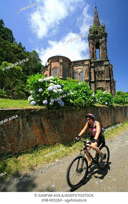 Girl biking in Furnas Valley, passing by a gothic style chapel  Azores islands, Portugal