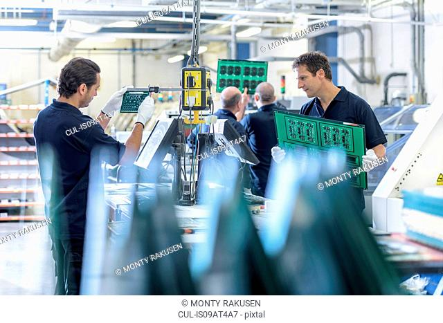 Workers inspecting circuit boards in circuit board factory