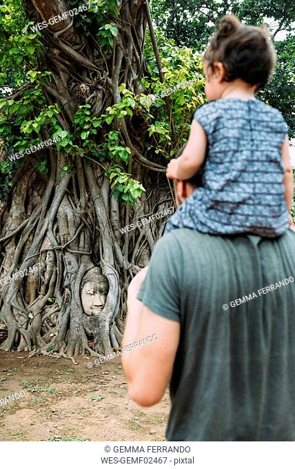 Thailand, Ayutthaya, Father and daughter visiting the Buddha head in between tree roots at Wat Mahathat