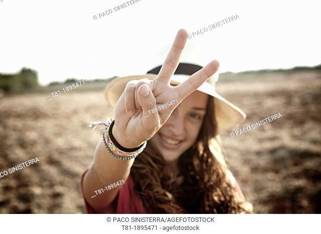 girl doing the peace sign, girl doing the peace sign