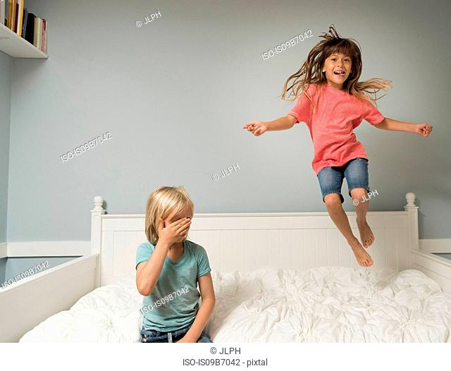 Girl in mid air jumping on bed