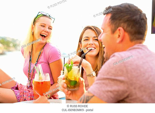 Three adult friends laughing over cocktails at waterfront restaurant, Majorca, Spain
