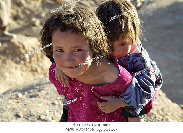 An ethnic Hazara girl carries her younger sibling on her back in the village of Ragshad, on the outskirts of Bamyan city in central Bamyan Province Afghanistan...