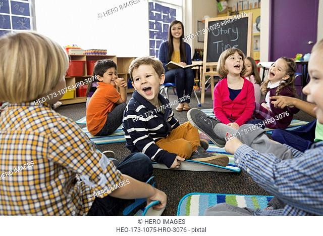 Cheerful students with teacher in elementary school during Story Time