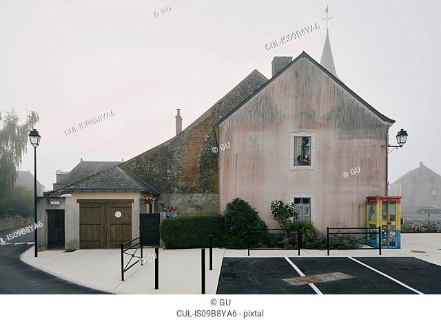 House gable and parking lot in Meigne-le-Vicomte village on misty morning, Loire Valley, France