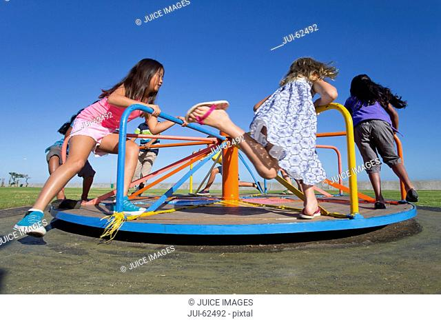 Children riding carousel in park