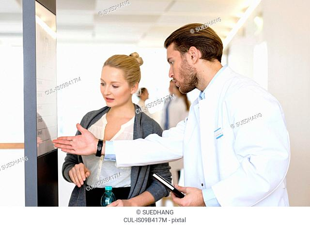 Male doctor and woman having discussion in hospital corridor