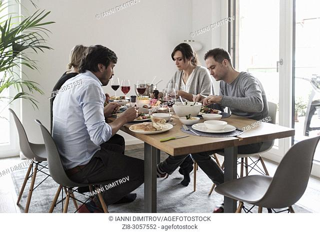 Vegetarian Sunday Lunch-Group of friends casually snacking on a selection of food while laughing and enjoying themselves