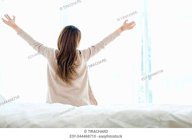 Back view of happy beautiful young Asian woman waking up in morning, sitting on bed, stretching in cozy bedroom, looking through window