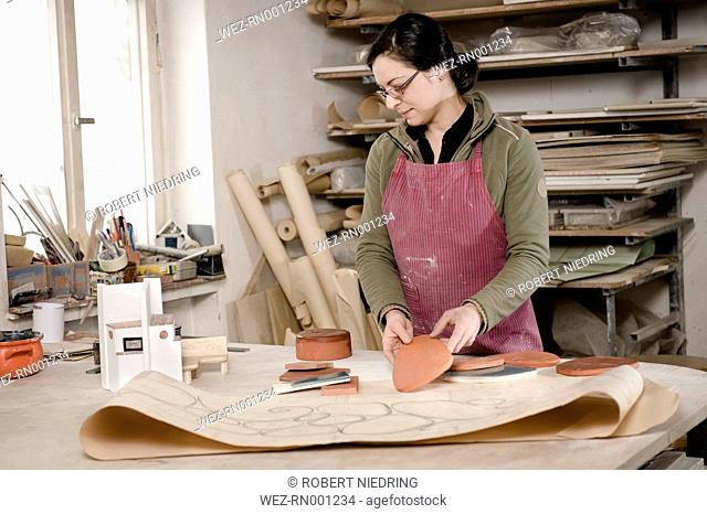 Germany, Bavaria, Mid adult woman supervising colour of tiles in workshop