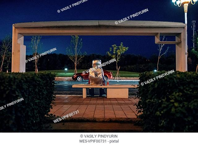 Spaceman sitting on bench at a bus stop at night