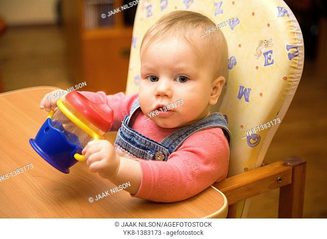 Happy Smiling Eight Month Old Infant Girl with Cup in High Chair