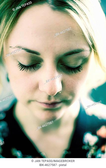 Young woman with closed eyes and nose piercing, portrait, Germany